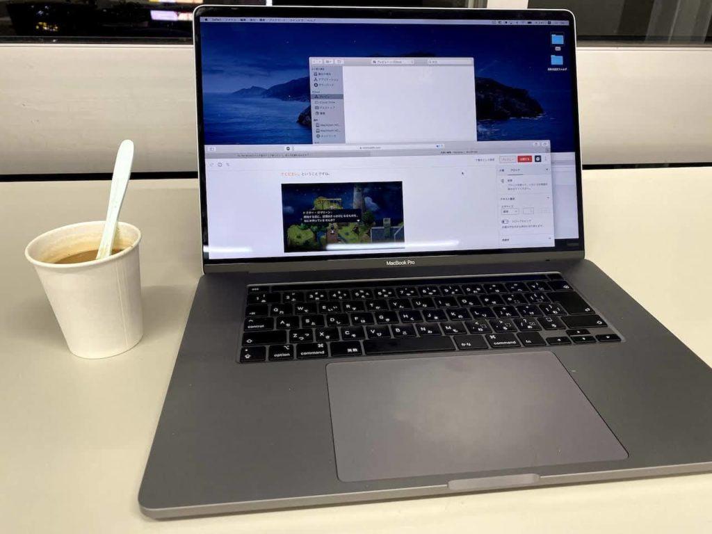 ノートパソコンと紙コップに入ったコーヒー