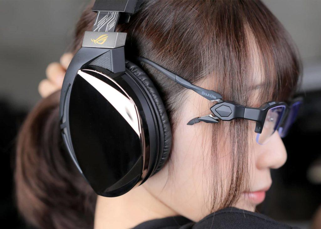 女性がゲーミングメガネをかけてヘッドホンを付けている