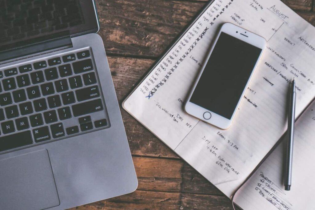 ノートパソコンとスマートフォンと手帳とペンが机の上に置いてある